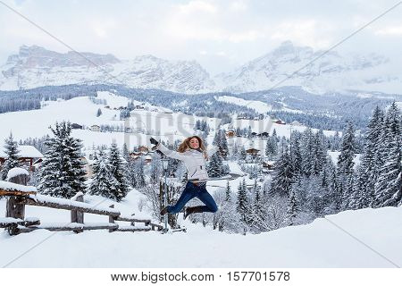 Happy girl jumping in the mountains during white wintertime