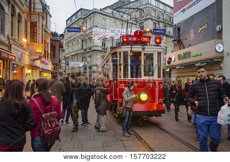 Istanbul Turkey - December 29 2013: Historic tram on Istiklal Avenue. People from different countries create cultural mosaics on this street. Istiklal Avenue in the Beyoglu district of Istanbul. A historic tram in front of the Beyoglu station of Tunel (18