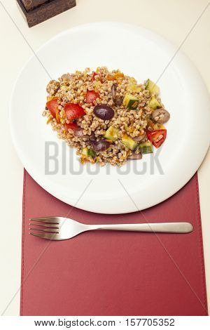 Spelt salad with vegetables served on white plate in restaurant healthy food