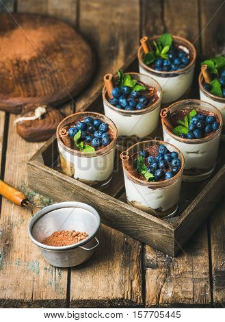 Homemade Tiramisu dessert in glasses with cinnamon, mint and fresh blueberries in wooden tray and sieve with cocoa powder over rustic wooden background, selective focus, vertical composition