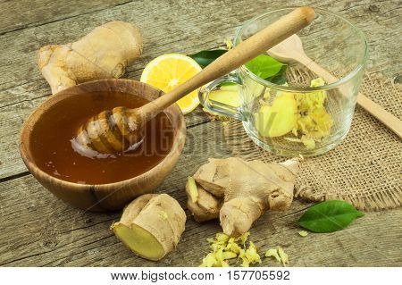 Preparing ginger tea against influenza. Traditional treatment for colds. Ginger, lemon and honey bowl on wooden table. Rustic wooden background. Home Pharmacy.