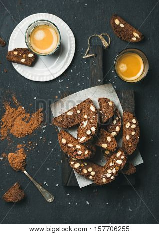 Dark chocolate and sea salt Biscotti with almonds and two glasses of coffee espresso on dark stone background, top view, selective focus, vertical composition