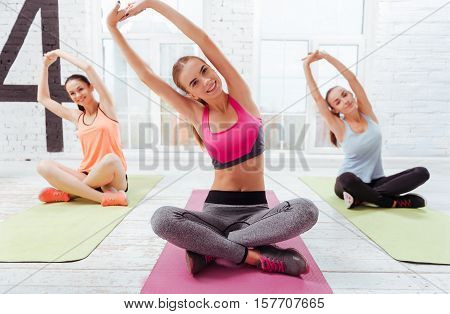 Lets do it. Three young beautiful girls having morning yoga and doing exercises while spending time in a gym.