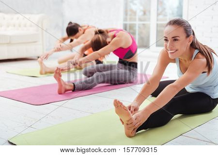 Together funnier. Three young delighted girls having group training while doing stretching exercises and spending time in a gym.