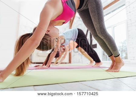 Keep fit. Three active young girls exercising together while having group training and spending time in fitness studio.