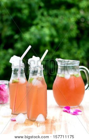 Rhubarb hibiscus drink iced tea with rose petals in the garden
