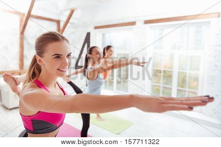 Concentrate on thoughts. Three happy young women standing in gym and doing stretching exercises while training together.