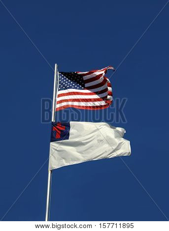 American flag and Christian flag fly side by side on a pole in Arkansas. They are framed by vivid blue sky and light wind blows them open.