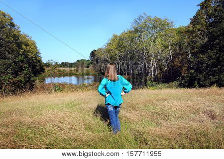 Young woman stands and admires the wild nature of Northern Louisiana. She has on jeans and a turquoise shirt.