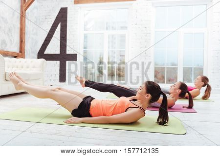 Training goals. Three active young women exercising hard and training while spending time in a gym.