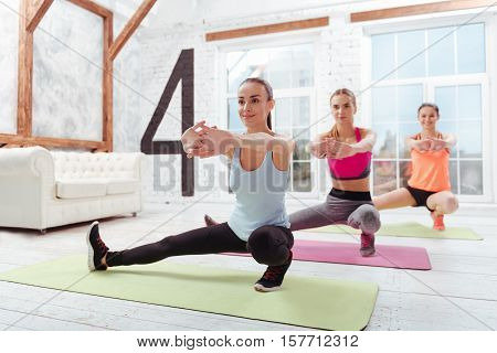 Perfect figure. Three slim young women exercising and spending time in fitness studio while smiling.