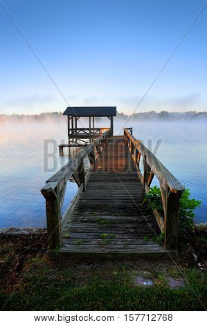 Wooden walkway leads to dock over calm waters of early morning on Lake Chicot in Lake Village Arkansas. Dock is weathered and rays of sun tint it golden.