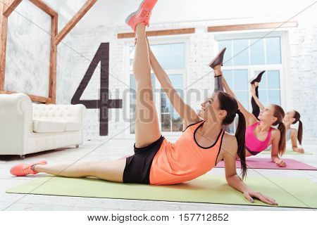 Achieve the split. Three young slim women doing stretching and exercising in groups while spending time in a gym.
