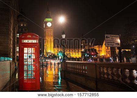 Popular tourist Big Ben and Houses of Parliament with red phone booth in night lights illumination in London, England, United Kingdom