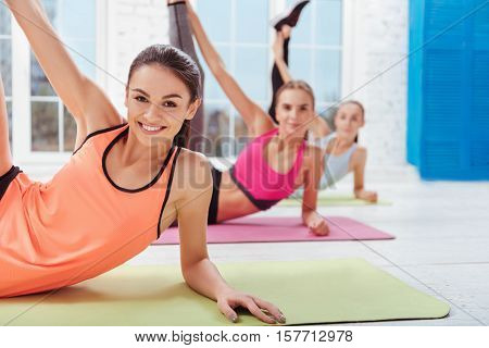 Improve flexibility. Three young delighted women enjoying stretching and doing exercises while smiling in a gym.