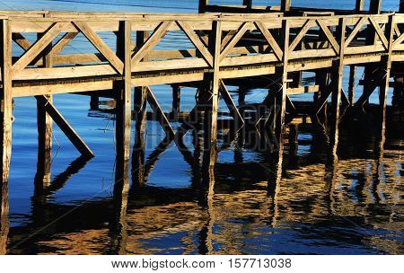 Old wooden fishing dock extends out onto Lake Chicot in Lake Village Arkansas. Closeup shows reflection rippling in the blue water.