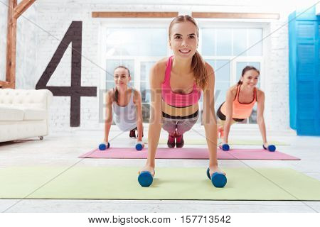 Strong body. Three smiling young women standing in plank and using dumbbells while exercising in a gym.