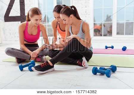 All things are done. Three young joyful women using smartphone and sitting in a gym together after having training.