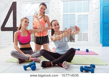 Nice shot. Three young joyful women making selfie after having training while posing in a gym.