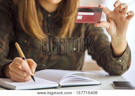 Girl writing in notepad and holding credit card