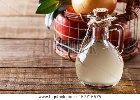 Apple cider vinegar and basket of apples over rustic wooden background close up