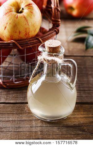Bottle of unfiltered apple cider vinegar over rustic wooden background close up