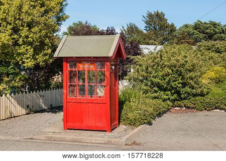 old-fashioned red telephone booth in public garden