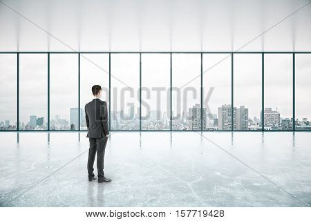 Thoughtful businessman standing in spacious unfurnished concrete interior with no view. 3D Rendering