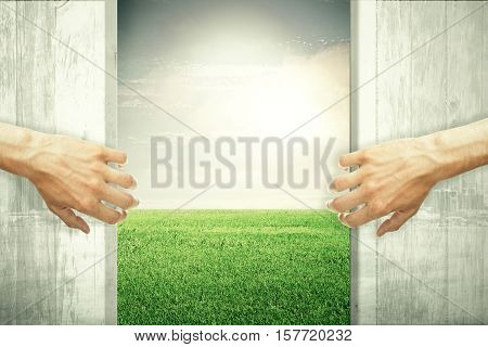 Hands opening abstract wooden doors revealing green meadow view. Nature concept