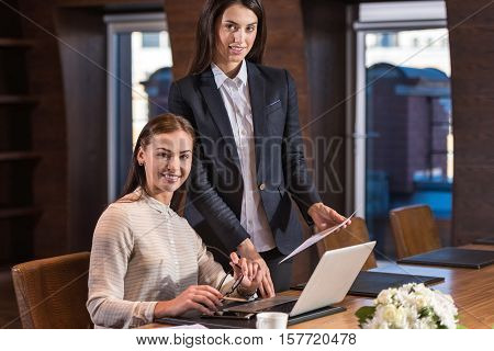 Beautiful and ambitious. Pretty young female colleagues posing in an office while working and making project together.
