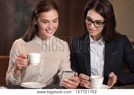 Time to rest. Joyful female young colleagues having a break with tea and using smartphone after working in an office.