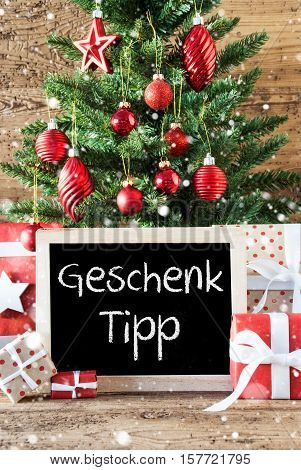 Chalkboard With German Text Geschenk Tipp Means Gift Tip. Colorful Christmas With Tree With Balls And Snowflakes. Gifts Or Presents In The Front Of Wooden Background.
