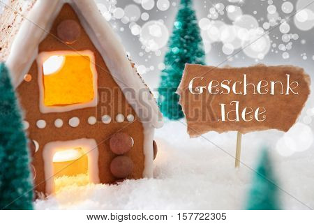 German Text Geschenk Idee Means Gift Idea. Gingerbread House In Snowy Scenery As Christmas Decoration. Trees And Candlelight For Romantic Atmosphere. Silver Background With Bokeh Effect.