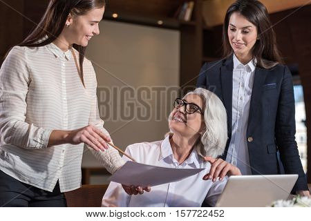 Giving a counsel. Two young female colleagues discussing their work results with boss while sharing ideas and working hard.