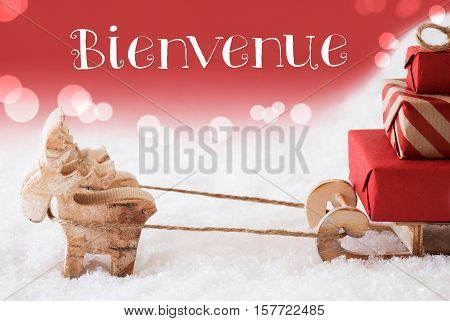 Moose Is Drawing A Sled With Red Gifts Or Presents In Snow. Christmas Card For Seasons Greetings. Red Christmassy Background With Bokeh Effect. French Text Bienvenue Means Welcome