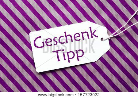 German Text Geschenk Tipp Means Gift Tip. One Label On A Purple Striped Wrapping Paper. Textured Background. Tag With Ribbon.