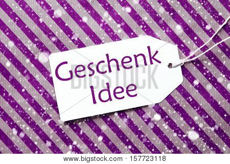 German Text Geschenk Idee Means Gift Idea. One Label On A Purple Striped Wrapping Paper. Textured Background With Snowflakes. Tag With Ribbon.
