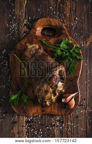 Whole roasted pork knuckle,  wooden brown background