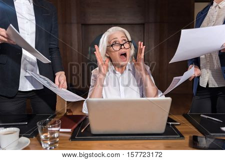 So tired. Exhausted angry elderly boss shouting at her colleagues while making project and working in an office.