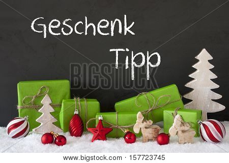 German Text Geschenk Tipp Means Gift Tip. Green Gifts Or Presents With Christmas Decoration Like Tree, Moose Or Red Christmas Tree Ball. Black Cement Wall As Background With Snow.