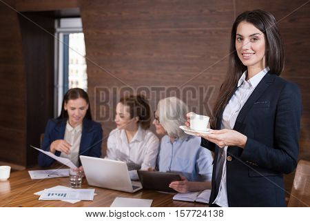 Best company. Pretty young smiling woman posing and drinking tea while her colleagues working in an office.