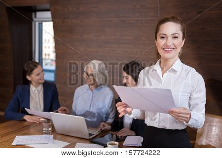 Happy to work here. Delighted young pretty woman posing and holding documents while her colleagues working on project in office.