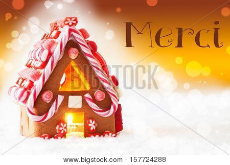 Gingerbread House In Snowy Scenery As Christmas Decoration. Candlelight For Romantic Atmosphere. Golden Background With Bokeh Effect. French Text Merci Means Thank You