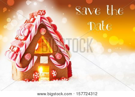 English Text Save The Date. Gingerbread House In Snowy Scenery As Christmas Decoration. Candlelight For Romantic Atmosphere. Golden Background With Bokeh Effect.