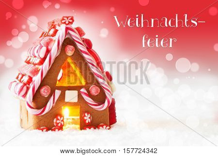 German Text Weihnachtsfeier Means Christmas Party. Gingerbread House In Snowy Scenery As Christmas Decoration. Candlelight For Romantic Atmosphere. Red Background With Bokeh Effect.