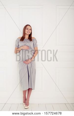 Mid shot of pregnant woman posing over white background. Holding her pregnant belly. Young smiling beautiful pregnant woman in grey loose dress