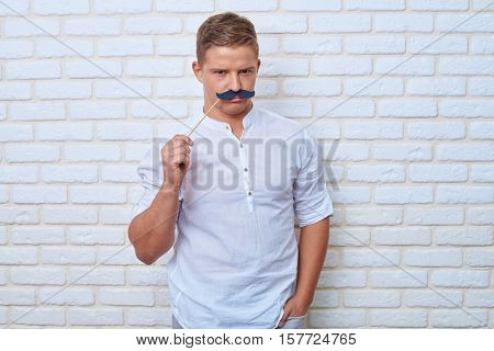 Mid shot of handsome boy frowning when wearing black paper moustache on stick. Looking at camera and smiling while standing with one hand in pocket on a white brick wall background