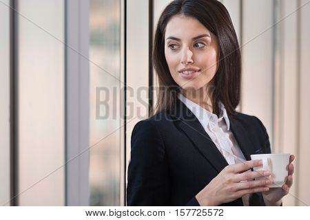 Enjoying the break. Brunette young pretty woman drinking coffee in an office after working and making project.