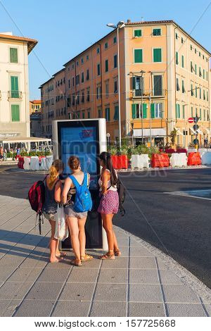 Livorno, Italy - July 01, 2016: Unidentified Young Women At A Digital Information Board In Livorno.