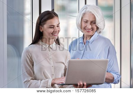 Through generations. Young pretty woman and her elderly elegant boss working and using laptop while standing together in an office.